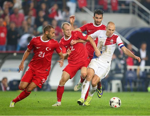 Turkey's Omer Toprak, left, and Semih Kaya, centre, in action with Arjen Robben of Netherlands during their World Cup Group D qualifying soccer match at Sukru Saracoglu Stadium in Istanbul, Turkey,  T