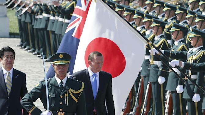 Australian Prime Minister Tony Abbott, center, reviews an honor guard during a welcome ceremony with Japanese Prime Minister Shinzo Abe, left, at Akasaka State Guest House in Tokyo Monday, April 7, 2014. Abbott is on a four-day official visit. (AP Photo/Koji Sasahara)