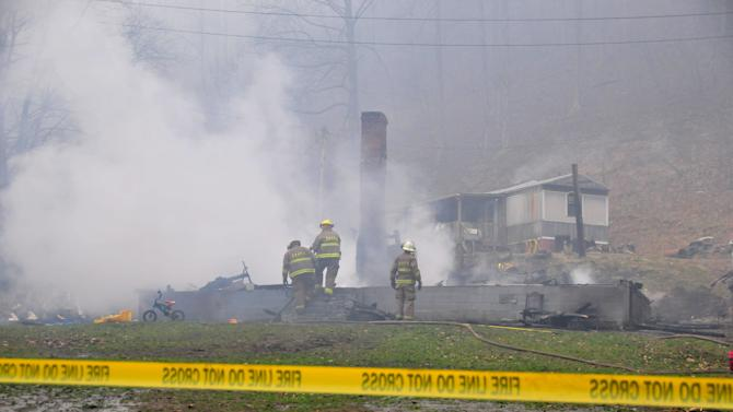 Firefighters from the Shelby Valley Volunteer Fire Department work Wednesday, Jan. 9, 2013, to extinguish a blaze at a home in Jonancy, Ky., which officials say killed four children and one adult and injured another adult. The blaze remains under investigation by Kentucky State Police. (AP Photo/Appalachian News-Express, Chris Anderson) MANDATORY CREDIT