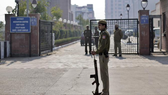 A Delhi policeman stands guard near the gate of a district court where the accused in a gang rape are undergoing trial, in New Delhi, India, Thursday, Jan. 24, 2013. The trial of five men charged with the gang rape and murder of a 23-year-old student on a New Delhi bus began in a closed courtroom Thursday with opening arguments by the prosecution lawyers in a special fast-track court set up just weeks ago to handle sexual assault cases. (AP Photo/ Altaf Qadri)