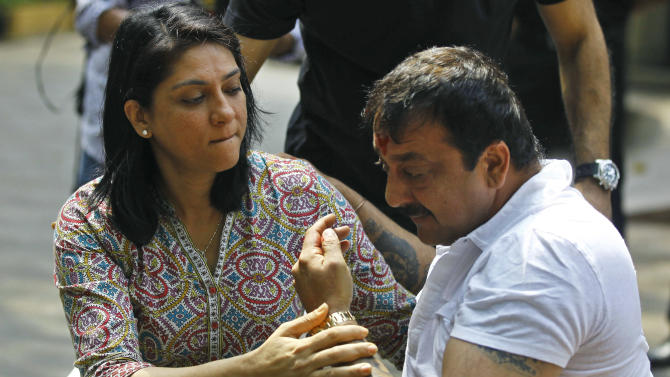 Indian Bollywood actor Sanjay Dutt, right, breaks down as his sister Priya Dutt tries to console him during a press conference at his residence in Mumbai, India, Thursday, March 28, 2013. Dutt said he has not sought pardon for a 1993 weapons conviction and will serve his prison sentence as ordered by India's Supreme Court. Dutt broke his silence a week after the court sentenced him to five years in prison for illegal possession of weapons supplied by Mumbai crime bosses linked to a 1993 terror attack that killed 257 people. (AP Photo/Rafiq Maqbool)
