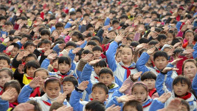 Children salute during a flag-raising ceremony on the first day of their new semester at a primary school in Bozhou