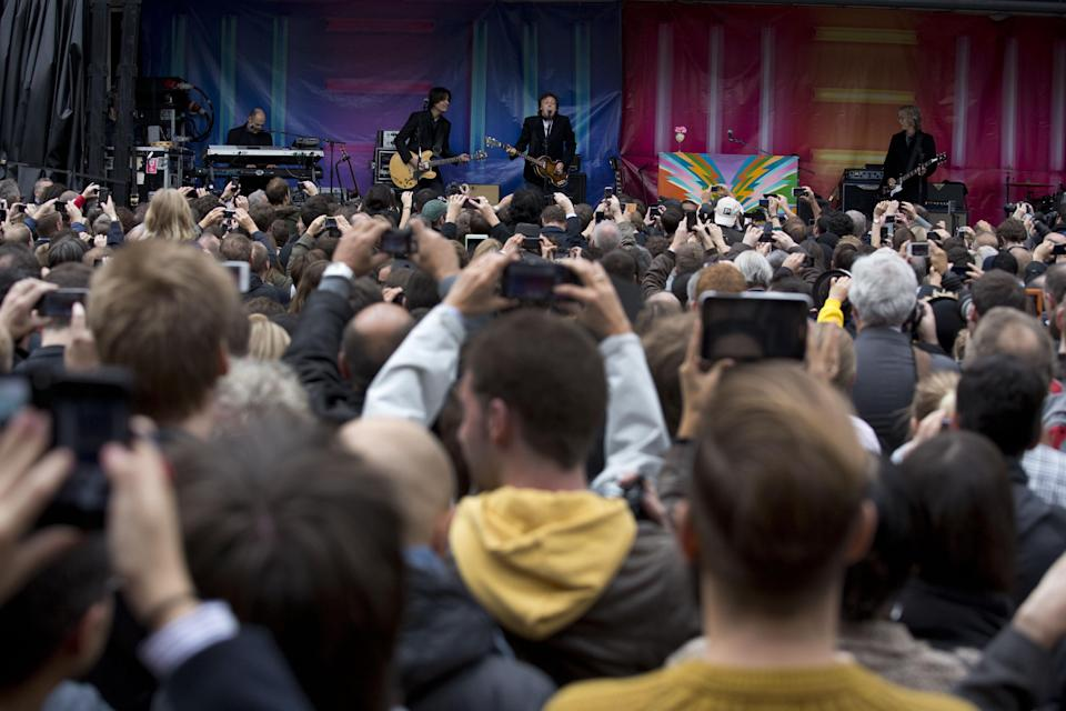 Sir Paul McCartney, center, plays a surprise gig in Covent Garden, London, Friday, Oct. 18, 2013. The surprise gig lasted for 20 minutes during lunchtime following a similar appearance in New York last Friday. (AP Photo/Matt Dunham)