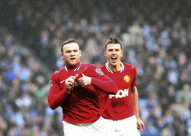 Manchester United's Wayne Rooney, left, celebrates his goal with Michael Carrick, right, during their FA Cup third round soccer match against Manchester City at the Etihad stadium, Manchester, England