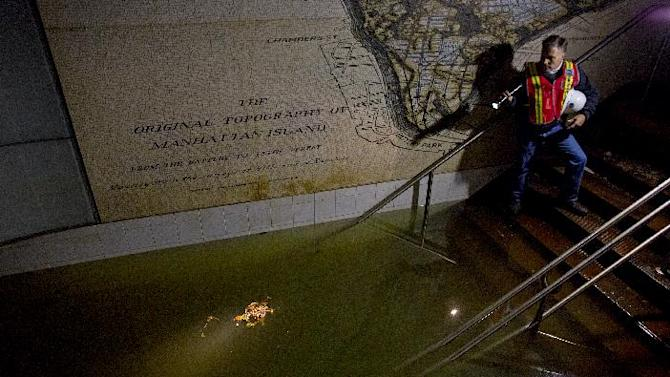 FILE - In this Wednesday, Oct. 31, 2012 file photo, Joseph Leader, Metropolitan Transportation Authority vice president and chief maintenance officer, shines a flashlight on standing water inside the South Ferry 1 train station in New York in the wake of Superstorm Sandy. A map of the original topography of Manhattan is seen on the wall behind Leader. By century's end, researchers forecast up to four feet higher seas, producing storm flooding akin to Sandy's as often as several times each decade. Even at current sea levels, Sandy's floodwaters filled subways, other tunnels and streets in parts of Manhattan. (AP Photo/Craig Ruttle, File)