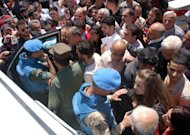 Handout photo the Syrian Arab News Agency shows Syrians surrounding UN observers during their visit to the central city of Homs. A car bomb rocked central Damascus on April 24, a day after nearly 60 were killed across Syria despite a hard-won ceasefire and the upcoming deployment of 300 UN peace monitors