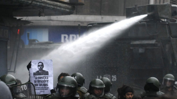 Riot police uses a water cannon to disperse a demonstration against the late Gen. Augusto Pinochet in Santiago, Chile, Sunday June 10, 2012.  Police used tear gas and water cannons to try to disperse hundreds of anti-Pinochet demonstrators protesting the premiere of a documentary, casting him as a national hero who saved Chile from communism, about the run-up to his dictatorship years.(AP Photo/Luis Hidalgo)