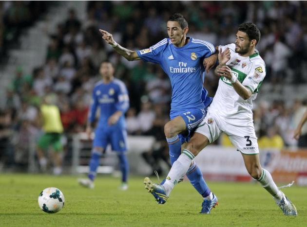 Real Madrid's Di Maria and Elche's Botia fight for ball during Spanish first division soccer match in Elche
