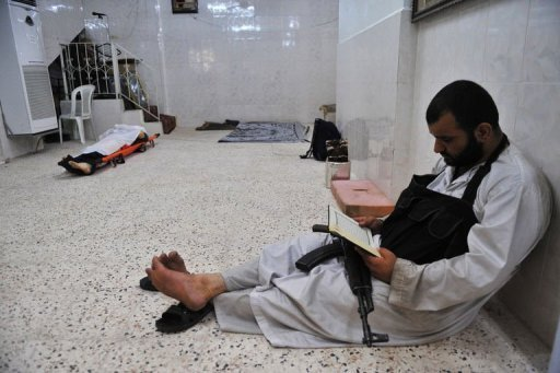 "A jihadist fighter reads the Quran next to the body of a civilian killed during clashes between Free Syrian Army rebels and Syrian regime troops in the center of Aleppo on August 13, 2012. The Organisation of Islamic Cooperation suspended Syria, saying the Muslim world ""can no longer accept a regime that massacres its people"""