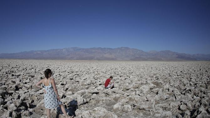 Eric Varone, right, takes a picture as Floriane Golay, of Switzerland watches, in Death Vally National Park Friday, June 28, 2013 in Badwater, Calif. Excessive heat warnings will continue for much of the Desert Southwest as building high pressure triggers major warming in eastern California, Nevada, and Arizona. (AP Photo/Chris Carlson)