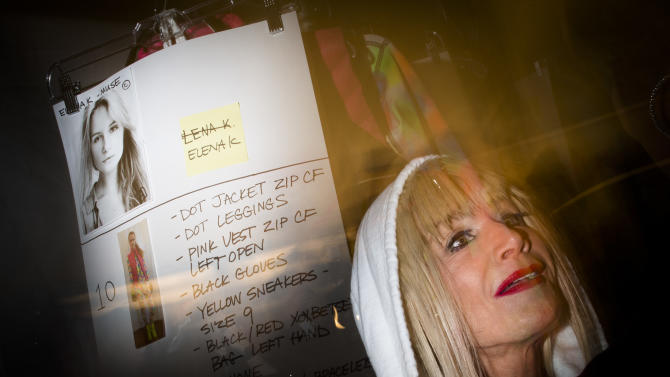 In this photo made with a long exposure and flash, designer Betsey Johnson is interviewed backstage before her Fall 2013 fashion show during Fashion Week, Monday, Feb. 11, 2013, in New York. (AP Photo/John Minchillo)