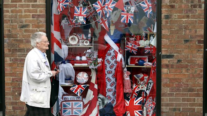 A member of the public is seen walking past a shop window with a display in honour of Britain's Queen Elizabeth II Diamond Jubilee in Yarm, England, Thursday, May 31, 2012. AP Photo/Scott Heppell)