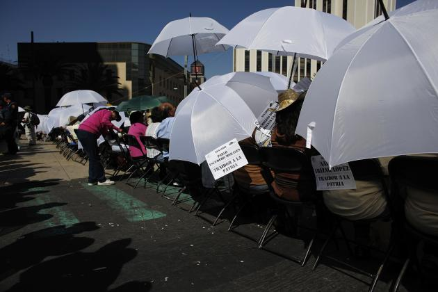 Demonstrators shield themselves from the sun with umbrellas as they sit in front of riot policemen during a protest against the energy reform bill in Mexico City