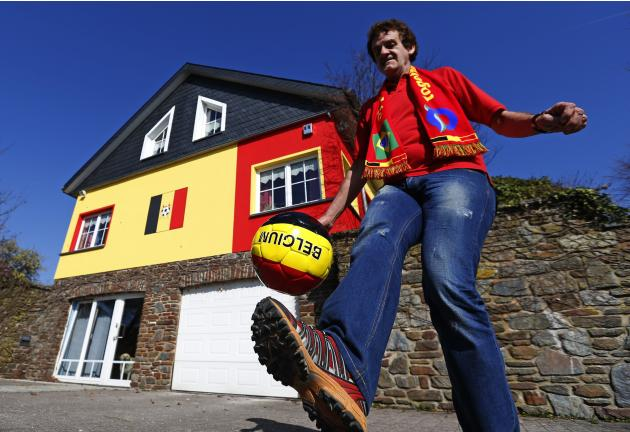 Belgian Wilfried Thelen attempts to balance a soccer ball with his foot outside his house that is painted in the colours of Belgium's national flag in Saint Vith