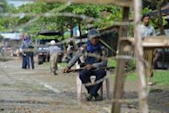 A policeman sits behind a barbed wire fence blocking the entrance into the Aung Mingalar quarter, turned into a ghetto after violence wracked the city of Sittwe, capital of Myanmar's western Rakhine state