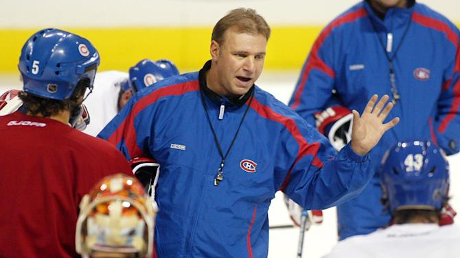 FILE - This Oct. 8, 2002 file photo shows Montreal Canadiens coach Michel Therrien  gesturing during a team practice in Montreal. The Canadiens have hired Therrien as their coach again. He was fired by the Canadiens during the 2002-03 season. (AP Photo/Paul Chiasson, File)