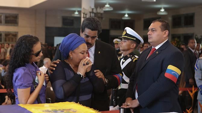 In this photo released by Miraflores Press Office, Colombian former senator Piedad Cordoba, center left, Hugo Chavez's daughter Rosa Virginia Chavez, left, and Venezuela's Vice President Nicolas Maduro stand next to the coffin containing the body of Venezuela's late President Hugo Chavez on display during his wake at a military academy where his body will lie in state until his funeral state in Caracas, Venezuela, Thursday, March 7, 2013.  While Venezuela remains deeply divided over the country's future, the multitudes who reached the president's coffin were united in grief and admiration for a man many considered a father figure. Chavez died on March 5 after a nearly two-year bout with cancer.(AP Photo/Miraflores Press Office)