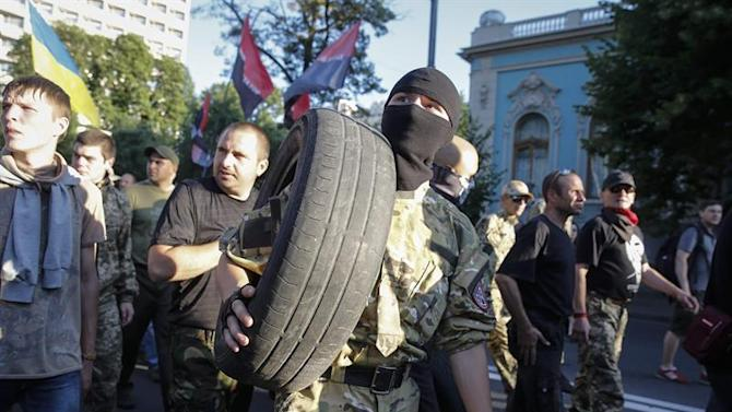 RPI17. Kiev (Ukraine), 03/07/2015.- Members and supporters of Right Sector and other ultra-right political parties carry tires during their protest in Kiev, Ukraine, 03 July 2015. About 1,000 ultra-right activists attended the protest demanding to release political prisoners, disaffirm the Minsk peace agreements and start liberate Ukrainian territory from pro-Russian separatists, according to Ukrainian local reports. (Protestas, Ucrania) EFE/EPA/ROMAN PILIPEY