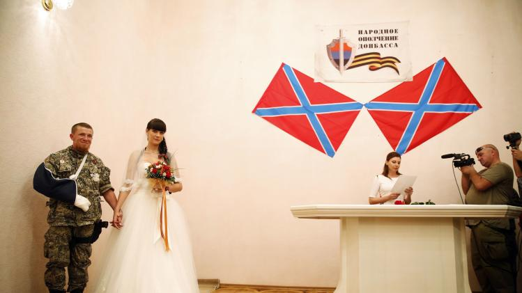 "Pro-Russian separatist Pavlov, call sign ""Motorola"", and his bride Elena attend a marriage ceremony in Donetsk"