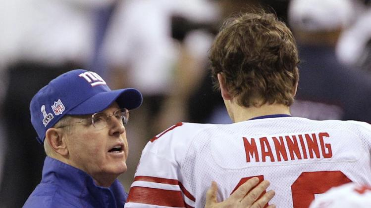 New York Giants head coach Tom Coughlin, left, greets quarterback Eli Manning on the field before their NFL Super Bowl XLVI football game against the New England Patriots, Sunday, Feb. 5, 2012, in Indianapolis. (AP Photo/David Duprey)