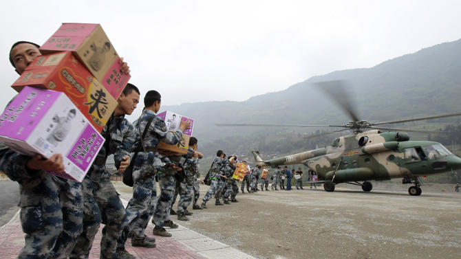 In this Sunday, April 21, 2013 photo, soldiers unload relief supplies from a helicopter at the quake ravaged Longmen township in Lushan county of southwest China's Sichuan province. Saturday's earthquake in Sichuan province killed at least 186 people, injured more than 11,000 and left nearly two dozen missing, mostly in the rural communities around Ya'an city, along the same seismic fault where a devastating quake to the north killed more than 90,000 people in Sichuan and neighboring areas five years ago in one of China's worst natural disasters. (AP Photo) CHINA OUT