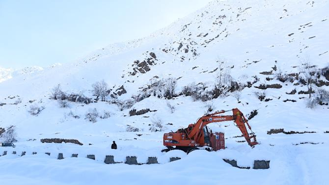 An Afghan policeman keeps watch as an excavator clears snow from a road near an avalanche site at Dara Keraman district of Panjshir province, north of Kabul on February 26, 2015