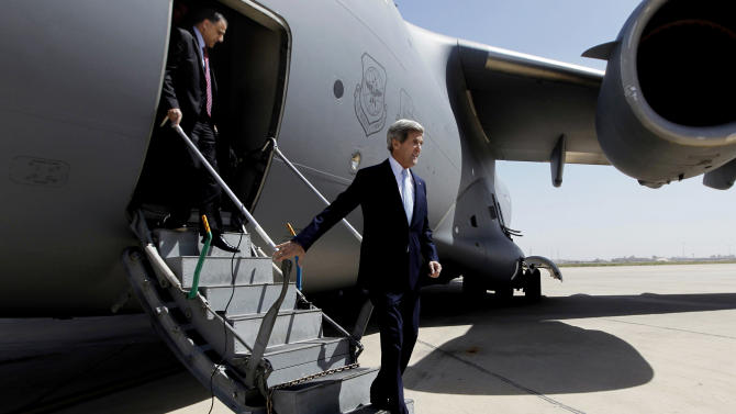 U.S. Secretary of State John Kerry, right, arrives to meet with Iraq's Prime Minister Nouri al-Maliki, not pictured, in Baghdad, Iraq, Sunday, March 24, 2013. Kerry made an unannounced visit to Iraq on Sunday and will urge al-Maliki to make sure Iranian flights over Iraq do not carry arms and fighters to Syria, a U.S. official said.  (AP Photo/Jason Reed, Pool)