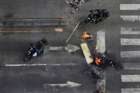 National guards ride their motorbikes past a barricade while looking for anti-government protesters during a protest against Nicolas Maduro's government at Altamira square in Caracas