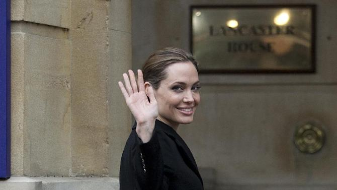Actress Angelina Jolie waves to the media as she arrives for the start of a G8 Foreign Ministers meeting in London, Thursday, April, 11, 2013. The ministers are meeting in London as Britain currently holds the G8 Presidency, with the heads of government G8 meeting set for June in Northern Ireland.(AP Photo/Alastair Grant)