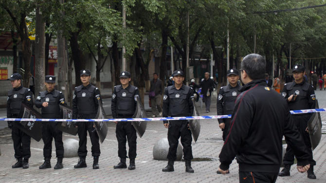 A man walk past policemen standing guard near a road leading to the site of Thursday's explosion in Urumqi, China's northwestern region of Xinjiang, Friday, May 23, 2014. Authorities closed the street market after attackers hurled bombs from two SUVs that plowed through shoppers on Thursday, killing dozens and wounding more than 90. (AP Photo/Andy Wong)