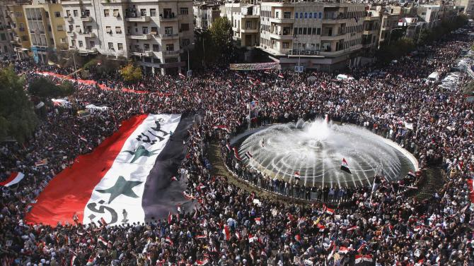 Pro-Syrian regime protesters, carry a giant Syrian flag during a demonstration against the Arab League decision to suspend Syria, in Damascus, Syria, on Sunday Nov. 13, 2011. Tens of thousands of pro-regime demonstrators gathered in a Damascus square Sunday to protest the Arab League's vote to suspend Syria over its bloody crackdown on the country's eight-month-old uprising. Saturday's Arab League decision was a sharp rebuke to a regime that prides itself as a bastion of Arab nationalism, but it was unlikely to immediately end a wave of violence that the U.N. estimates has killed more than 3,500 people since mid-March. (AP Photo/Muzaffar Salman)