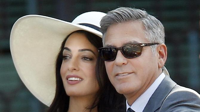 "FILE In this Sept. 29, 2014 file photo actor George Clooney and his wife Amal Alamuddin, arrives at the Cavalli Palace for their civil marriage ceremony in Venice, Italy. The Obama administration on Friday formally accused North Korea's government of being responsible for the dramatic hacker break-in at Sony Pictures Entertainment Inc. but offered few hints about how or whether it would retaliate. Its proof: The U.S. detected communications between computer Internet addresses known to be operated by North Korea and hacking tools left behind at the crime scene, which the FBI also said contained subtle clues linking them to that country's government. In Hollywood, Clooney said the entertainment industry should take action now by pushing for the immediate release of ""The Interview"" online. In an interview with the trade site Deadline, Clooney urged Sony to ""stick it online. Do whatever you can to get this movie out. Not because everybody has to see the movie, but because I'm not going to be told we can't see the movie. That's the most important part."" (AP Photo/Luca Bruno, File)"
