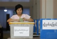 A woman votes at a ballot station during by-elections in Yangon