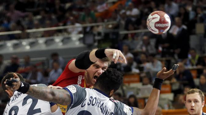 Rodriguez of Spain shoots over Luka Karabatic and Sorhaindo of France during their semi-final match of the 24th Men's Handball World Championship in Doha
