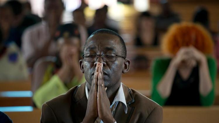 A man prays during a mass commemorating late South African President Nelson Mandela on December 8, 2013 in Soweto, near Johannesburg