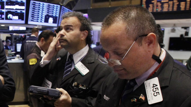 Traders work on the floor of the New York Stock Exchange, Monday, April 9, 2012, in New York. Stocks pulled back sharply at the open as Wall Street got its first chance to react to a slowdown in hiring in the United States in March. (AP Photo/Richard Drew)