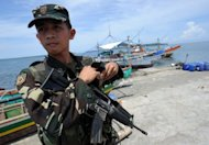 File photo shows a Filipino soldier standing guard next to fishing boats at a pier in Masinloc town in Zambales province, near Scarborough Shoal, on May 18. China said Monday it welcomed Philippine President Benigno Aquino's order pulling out two ships from the disputed shoal and expressed hope it would calm tensions