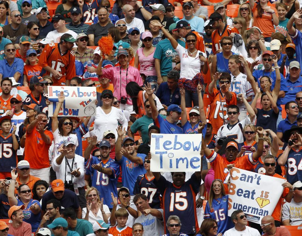 Fans cheer as Denver Broncos quarterback Tim Tebow walks onto the field during the first half of the Broncos' NFL football game against the Miami Dolphins, Sunday, Oct. 23, 2011, in Miami. (AP Photo/Hans Deryk)