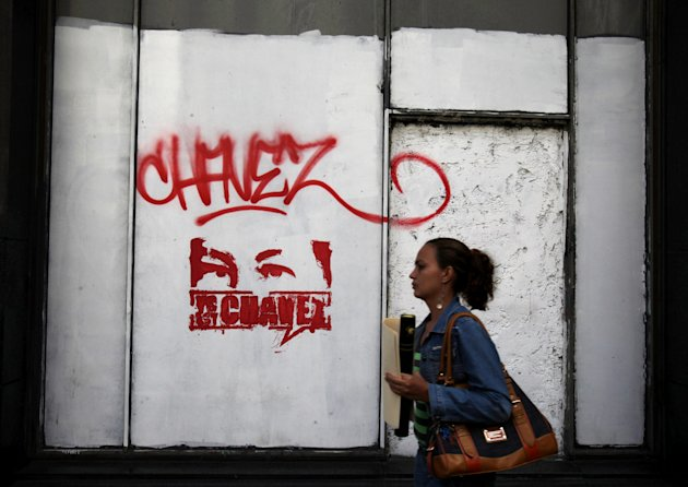 "A pedestrian walks before a stenciled graffiti that reads in Spanish: ""I am Chavez,"" in downtown Caracas, Venezuela, Thursday, Jan. 17, 2013. Venezuela's President Hugo Chavez, normally at the center of national attention, is so ill following a fourth cancer surgery in Cuba that he has made no broadcast statement in more than a month, and has not appeared in a single photo. During Chavez's five-week absence, some Venezuelans have begun speculating about whether his cancer could force him from office and require a new presidential election. (AP Photo/Fernando Llano)"