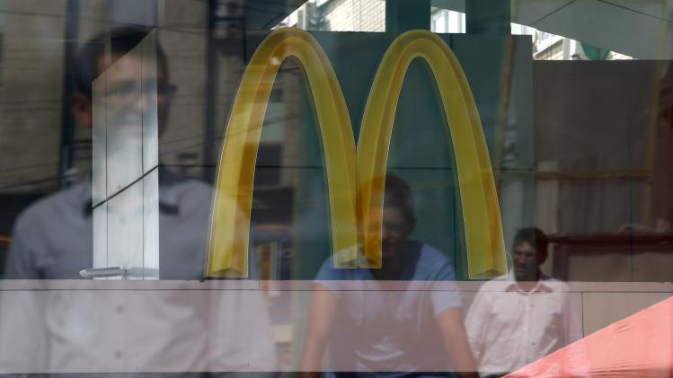 People are reflected in a window of a closed McDonald's restaurant, one of four temporarily closed by the state food safety watchdog, in Moscow