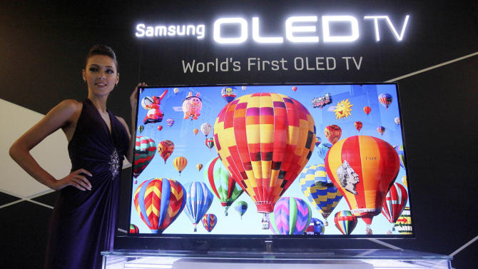 FILE - In this May 10, 2012 file photo, a model poses with a 55-inch Samsung OLED, or organic light-emitting diode, TV during a press conference in Seoul, South Korea. Long-time Japanese rivals Sony Corp. and Panasonic Corp. are working together to develop next-generation TV panels called OLEDs in a reversal of decades of rivalry as they try to catch up with South Korea's Samsung Electronics. The companies said in a joint statement Monday, June 25, they will share core technologies to develop OLED panels. They are aiming for low-cost mass production by 2013. (AP Photo/Ahn Young-joon, File)