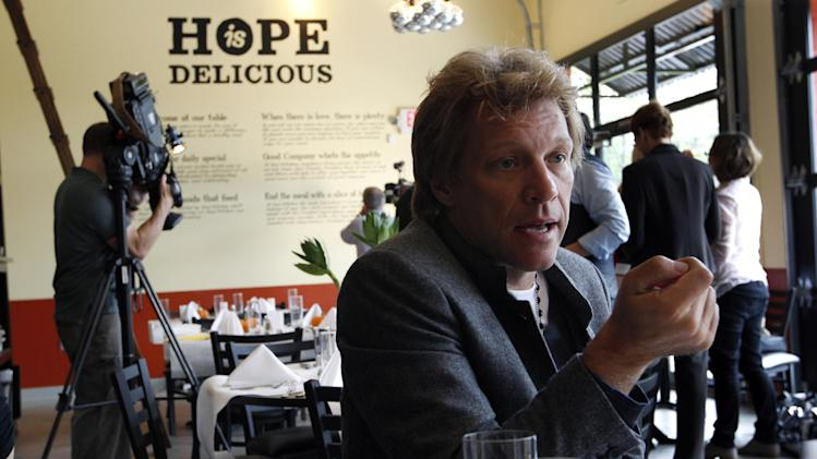 Rock star Jon Bon Jovi answers a question as he sits in the Soul Kitchen restaurant in Red Bank, N.J., Wednesday, Oct. 19, 2011, during the opening of the restaurant which is designed to help the hungry without the stigma of a soup kitchen. Diners pay whatever they're able to. (AP Photo/Mel Evans)