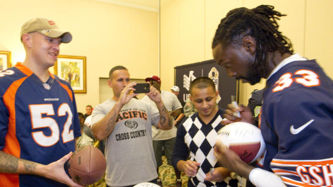 In this photo provided by IMG Consulting, Wyat Mayers, left,  Chris Walter, left center, Guny Aragon, center right, all members of the Warrior Transition Battalion, look on as Chicago Bears corner back Charles Tillman (33) autographs a football at Schofield Barracks Thursday, Jan. 24, 2013, in Honolulu. Several NFL All-Star football players, who will be playing in this weekend's Pro Bowl, joined the Warrior Transition Battalion for lunch and a autograph session at the USAA NFL sponsored event. (Eugene Tanner/AP Images for USAA. IMG Consulting