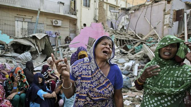 In this Saturday, Dec. 1, 2012 photo, members of Pakistani Hindu community react next to the rubble of a Hindu temple, which was destroyed on Saturday by a builder, in Karachi, Pakistan. Members of the Pakistan Hindu community in the southern port city of Karachi protested on Sunday over the destruction of a Hindu temple Saturday by a builder who claimed that the land is his. (AP Photo/Fareed Khan)