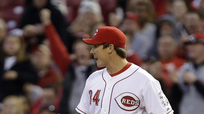 Cincinnati Reds starting pitcher Homer Bailey pumps his fist after covering first and making the out on Washington Nationals' Jayson Werth on a a close play in the third inning of a baseball game, Friday, April 5, 2013, in Cincinnati. (AP Photo/Al Behrman)