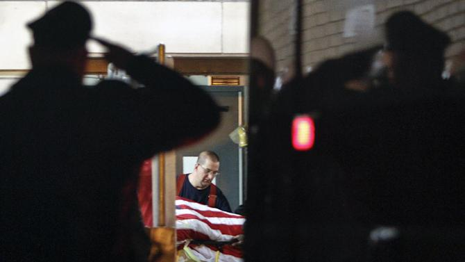 A police officer salutes as the body of fallen firefighter Capt. Michael Goodwin is brought to Thomas Jefferson Hospital in Philadelphia, Saturday, April 6, 2013. The fire caused a partial roof collapse that killed Goodwin and injured a colleague who was trying to rescue him, officials said. (AP Photo/ Joseph Kaczmarek)