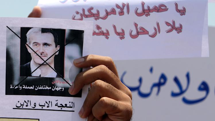 "Bahrainis, including many of Syrian origin, hold signs protesting the Syrian regime of President Bashar Assad after midday prayers Friday, Aug. 12, 2011, in Muharraq, Bahrain. The picture, showing a merged image of Assad and his father, the late Syrian leader Hafez Assad, says: ""Two sides of the same coin ... the father sheep and the son."" Writing behind includes: ""Bashar, American agent, go away."" In Syria, activists said Friday that Syrian government forces opened fire on thousands of anti-government protesters in the eastern Syrian city of Deir el-Zour following midday prayers at two mosques in that city. (AP Photo/Hasan Jamali)"