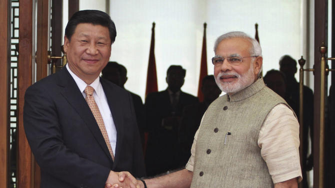 In this Wednesday, Sept. 17, 2014 file photo, Indian Prime Minister Narendra Modi, right, shakes hand with Chinese President Xi Jinping as he welcomes him at a hotel in Ahmadabad, India. Xi toasted the birthday of Modi in a quiet dinner earlier this week in Modi's home state and the two leaders are full of praise for one another, and one another's countries. Left largely unspoken, though, are the deep worries in India over Chinese maneuvering in the Indian Ocean, where New Delhi's years of dominance is being chipped away by billions of dollars in aid from Beijing and gargantuan Chinese construction projects. (AP Photo/Ajit Solanki, File)