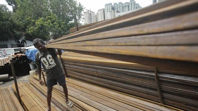 A worker loads iron rods in a truck at an iron and steel market in an industrial area in Mumbai September 11, 2013. REUTERS/Danish Siddiqui