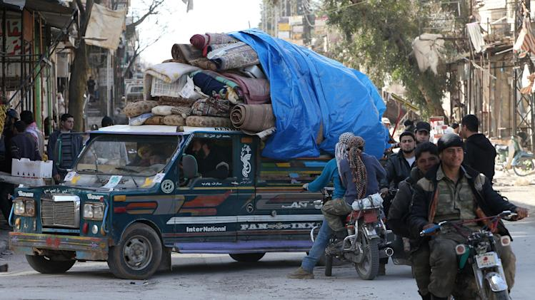 A Syrian family carry their house furniture on a pickup as they leave their home to a safer place, at Maarat al-Nuaman town, in Idlib province, Syria, Tuesday Feb. 26, 2013. Syrian rebels battled government troops near a landmark 12th century mosque in the northern city of Aleppo on Tuesday, while fierce clashes raged around a police academy west of the city, activists said. (AP Photo/Hussein Malla)